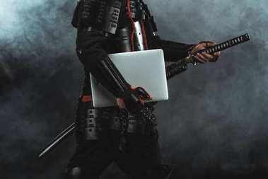 Cropped shot of samurai in traditional armor with laptop taking out sword on dark background with smoke stock vector