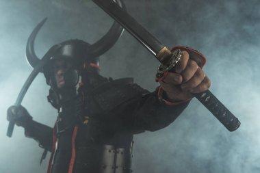 Close-up shot of samurai in armor with dual katana swords on dark background with smoke stock vector