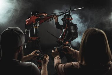 rear view of man and woman playing samurai fighting in real life with gamepads on black