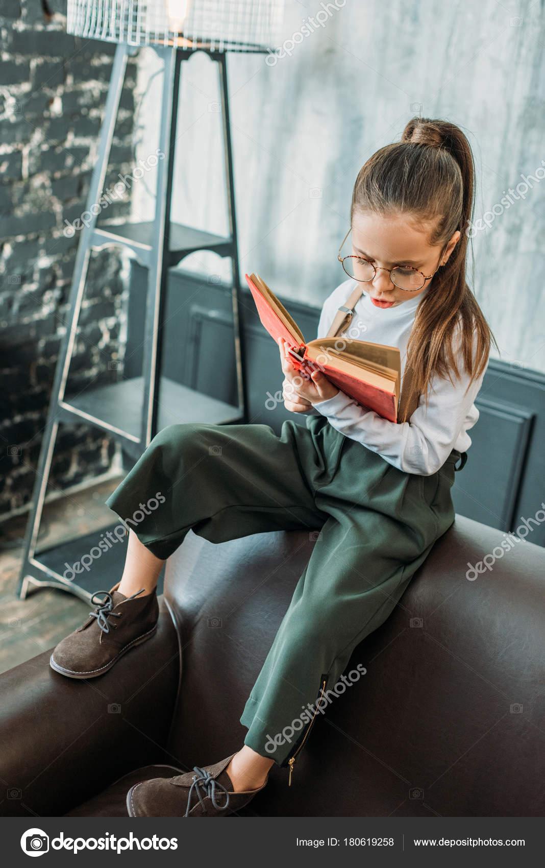 Concentrato piccolo bambino che legge libro mentre era seduto sul foto stock - Musica divano era ...