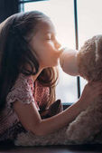 Fotografie beautiful little child kissing teddy bear in nose
