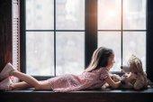 Seitenansicht des kleine Kind spielt mit Teddybär liegend auf Fensterbank
