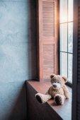 teddy bear on windowsill of stylish room in loft style