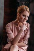 Detailní portrét krásná mladá žena v růžových šatech při pohledu na fotoaparát