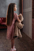 adorable little child holding teddy bear at loft apartments