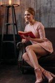 mladá žena s knihou sedící na gauči v interiéru podkroví