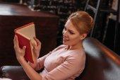 Fotografie krásná mladá žena čtení knihy zatímco sedí na gauči
