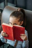 Detailní portrét vážným malé dítě pokrývající obličej s Červená kniha