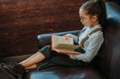 komoly kis gyerek otthon a fotelben ülve könyv