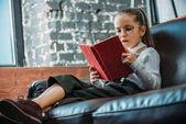 zaměřil čtení knihy na gauči doma malé dítě