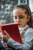 Fotografie Detailní portrét koncentrovaného malé dítě čtení knihy