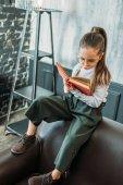 Koncentrovaná malé dítě, zatímco sedí na gauči čtení knihy