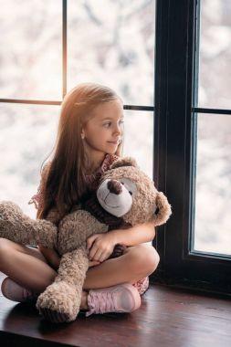 Beautiful little child sitting on windowsill with teddy bear stock vector