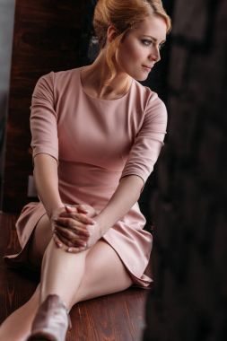 beautiful young woman in pink dress sitting on wooden floor and looking away