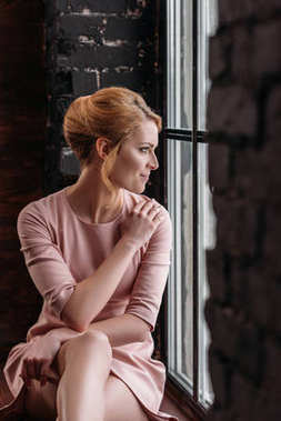 thoughtful young woman in pink dress sitting on windowsill