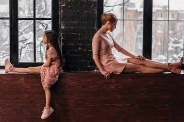 depressed mother and daughter sitting on windowsills back to back