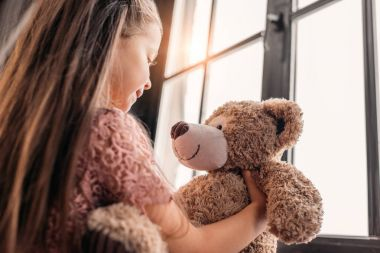 adorable little child playing with teddy bear on windowsill