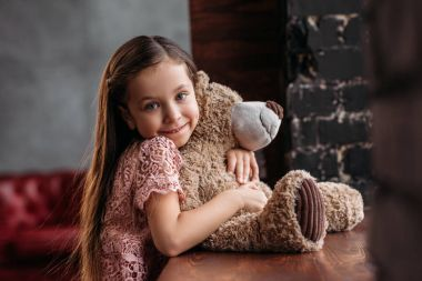 smiling little child embracing teddy bear at windowsill in loft apartments