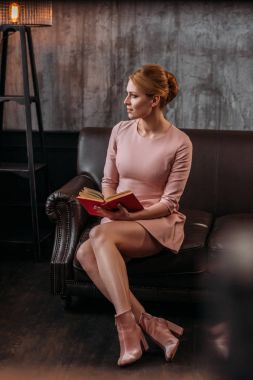 thoughtful young woman with book sitting on couch and looking away