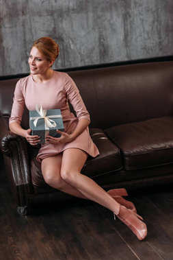 attractive young woman with valentines day gift sitting on couch in loft interior