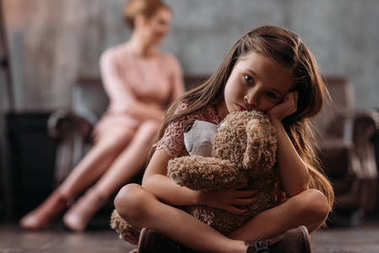 little depressed child sitting on floor with teddy bear while her mother sitting on couch