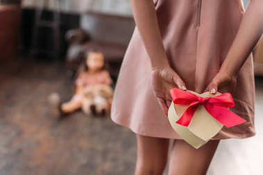 cropped shot of mother hiding birthday gift for daughter behind back