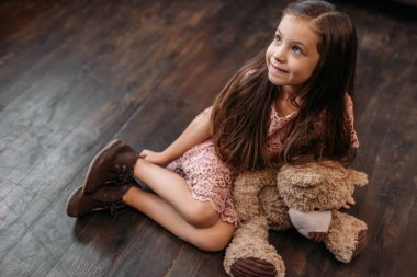 adorable little child sitting on floor with teddy bear