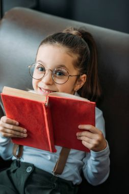 close-up portrait of happy little child with book on couch
