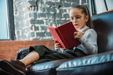focused little child reading book on couch at home