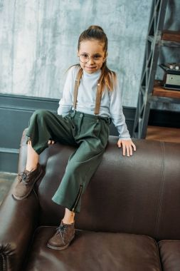 adorable little child in stylish clothing sitting on couch in loft apartments