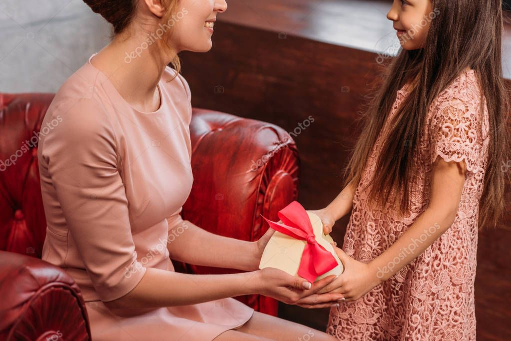 cropped shot of daughter giving present to mother for birthday