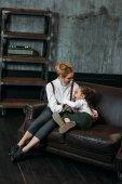 Fotografie matka a dcera objímat na gauči v podkrovní apartmány