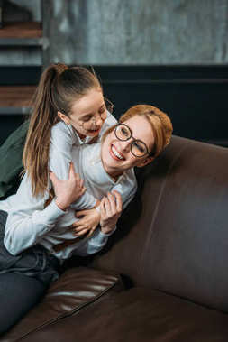 happy adorable daughter embracing her mother from behind on couch at home