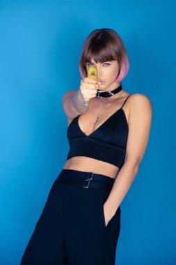 Stylish girl holding banana like shooting with gun isolated on blue stock vector