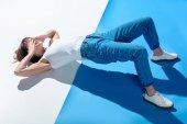 Fotografia ragazza alla moda che si trova sul pavimento, che copre gli occhi con le mani e facendo fianchi Sollevare