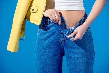 cropped image of stylish girl unbuttoning jeans isolated on blue