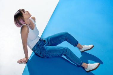 stylish girl sitting in shirt and jeans on white and blue floor