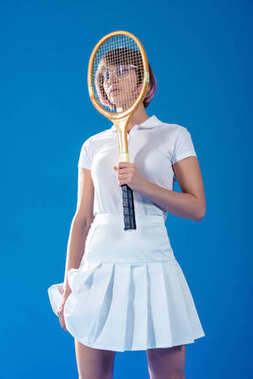 tennis player covering face with tennis racket isolated on blue