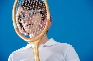 portrait of tennis player covering face with tennis racket isolated on blue