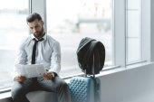 mladý podnikatel čtenářský deník při čekání na letadlo v letištní hale