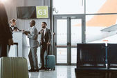 Photo businessmen standing at airport reception to buy tickets while colleague walking to them