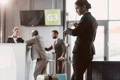 obchodník při čekání na letadlo v letištní hale při pohledu na hodinky