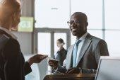 Fényképek boldog fiatal üzletember ad útlevél és jegy, repülőtér személyzete ellenőrizze a számláló