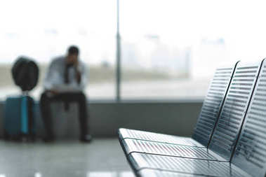 close-up shot of seats at airport lobby with buisnessman waiting for plane blurred on background