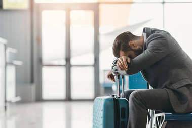 tired businessman sleeping at airport lobby while waiting for flight