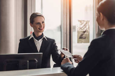 young businesswoman giving ticket to staff at airport check in counter