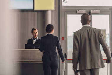 rear view of queue of businesspeople at airport check in counter