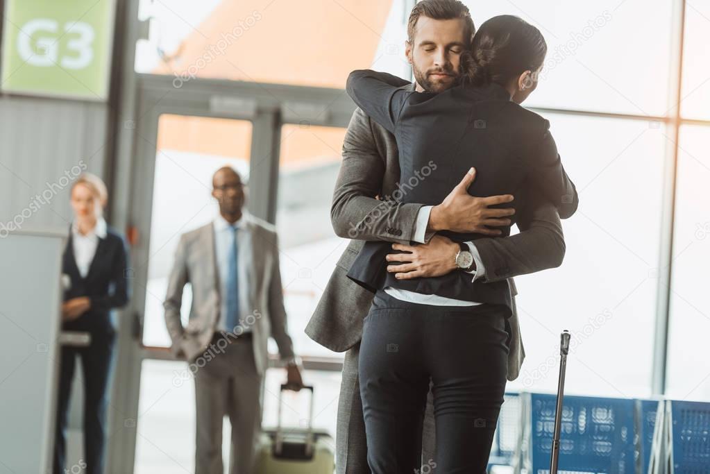 man embracing woman at airport after long separation