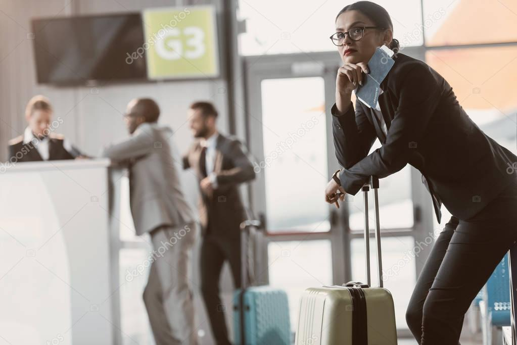 thoughtful young businessman waiting for flight at airport lobby