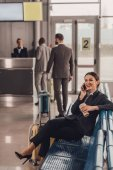 Photo young businesswoman waiting for plane at airport lobby and talking by phone